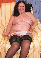 Plump in black stockings getting naked