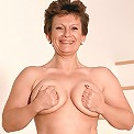 Sexy mature model playing with her round boobs and cramming her shaved slit with a dildo