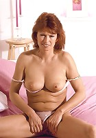 Naughty mature redhead showing off her wet cooter and cramming her slit with a dildo live