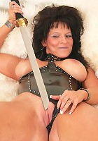 Nasty matured slut with melon jugs in BDSM suit threatening her pussy with a samurai