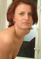 Gorgeous mature redhead posing seductively beside her window!