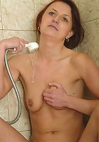 Short-haired older bitch letting the shower head bring her to orgasm!