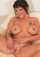 Mature babe with big tits rubbing her shaven pink slit