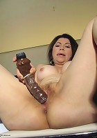 Horny housewife playing on her bed with a dildo
