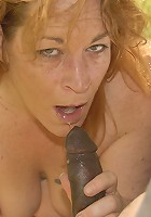 Horny red slut sucking on a big black pole