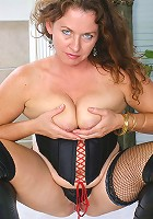 Intense looking MILF is hard at work playing with her pussy