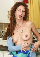 Foxy strips and fingers her pussy in the kitchen inside here
