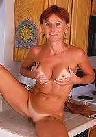 Redheaded MILF Kate spreads her tight asscheeks in the kitchen