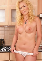 Older blond babe Caroline gets naked in the kitchen.