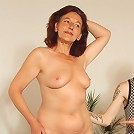 The redhead opens her robe and poses for the two guys painting her naked body